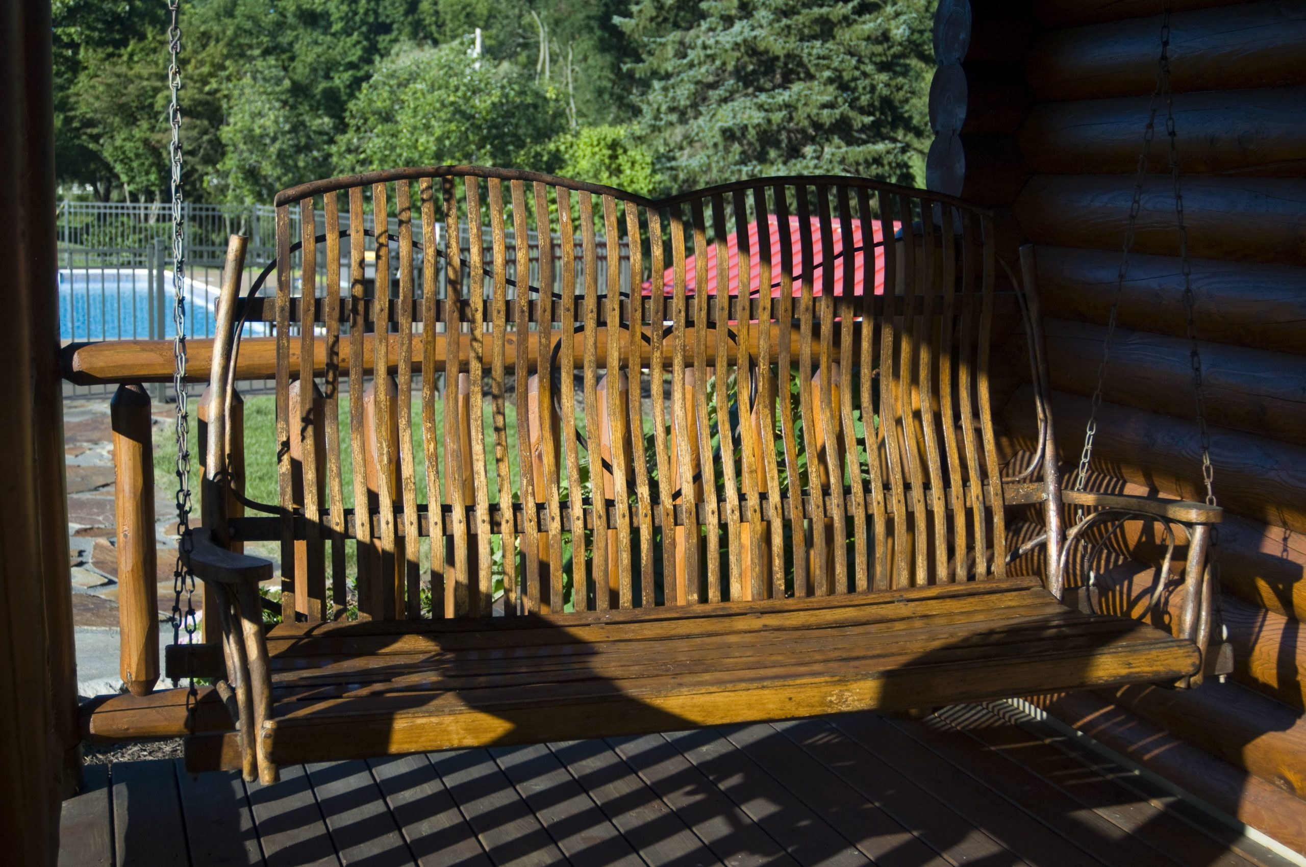 Swing bench on log cabin porch at Silvermist