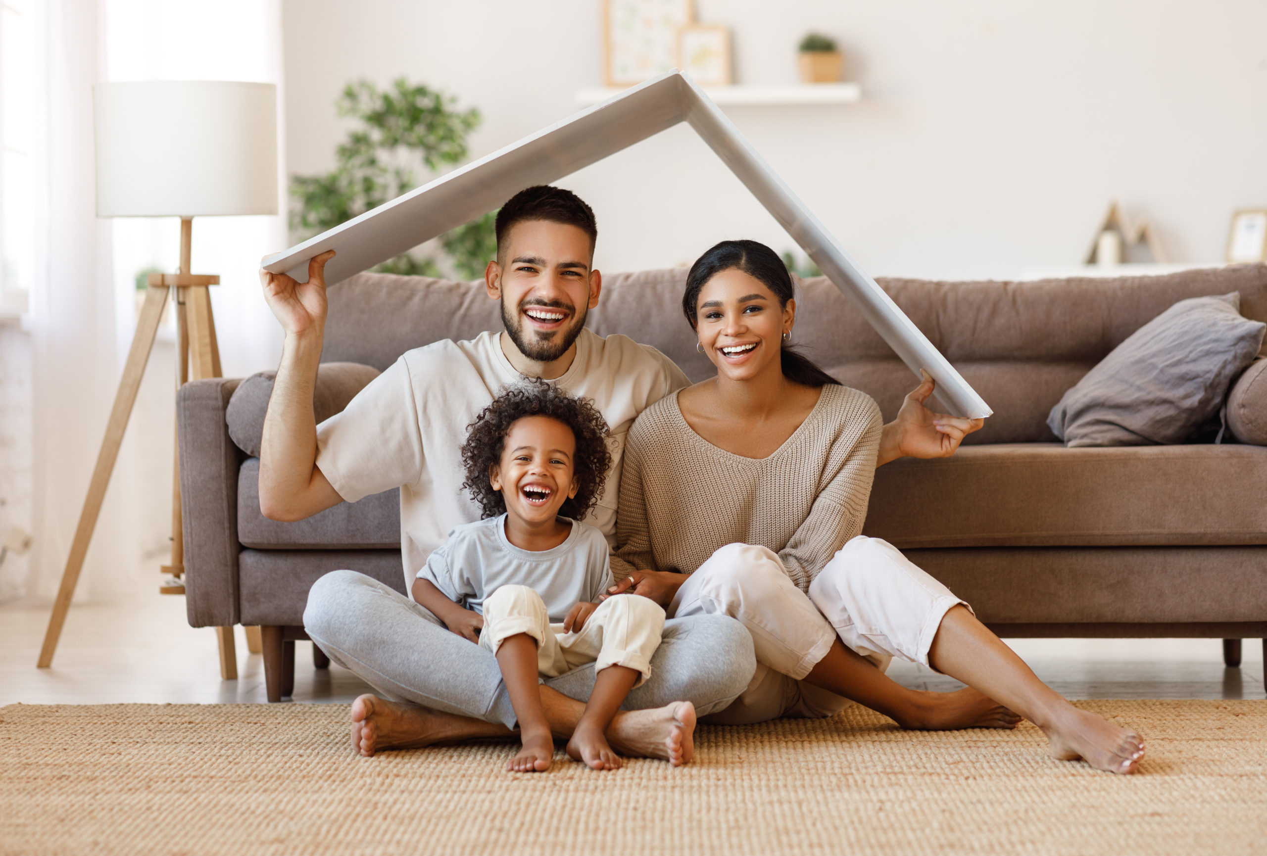 Cheerful parents with child smiling and keeping roof mockup over heads while sitting on floor in cozy living room during relocation