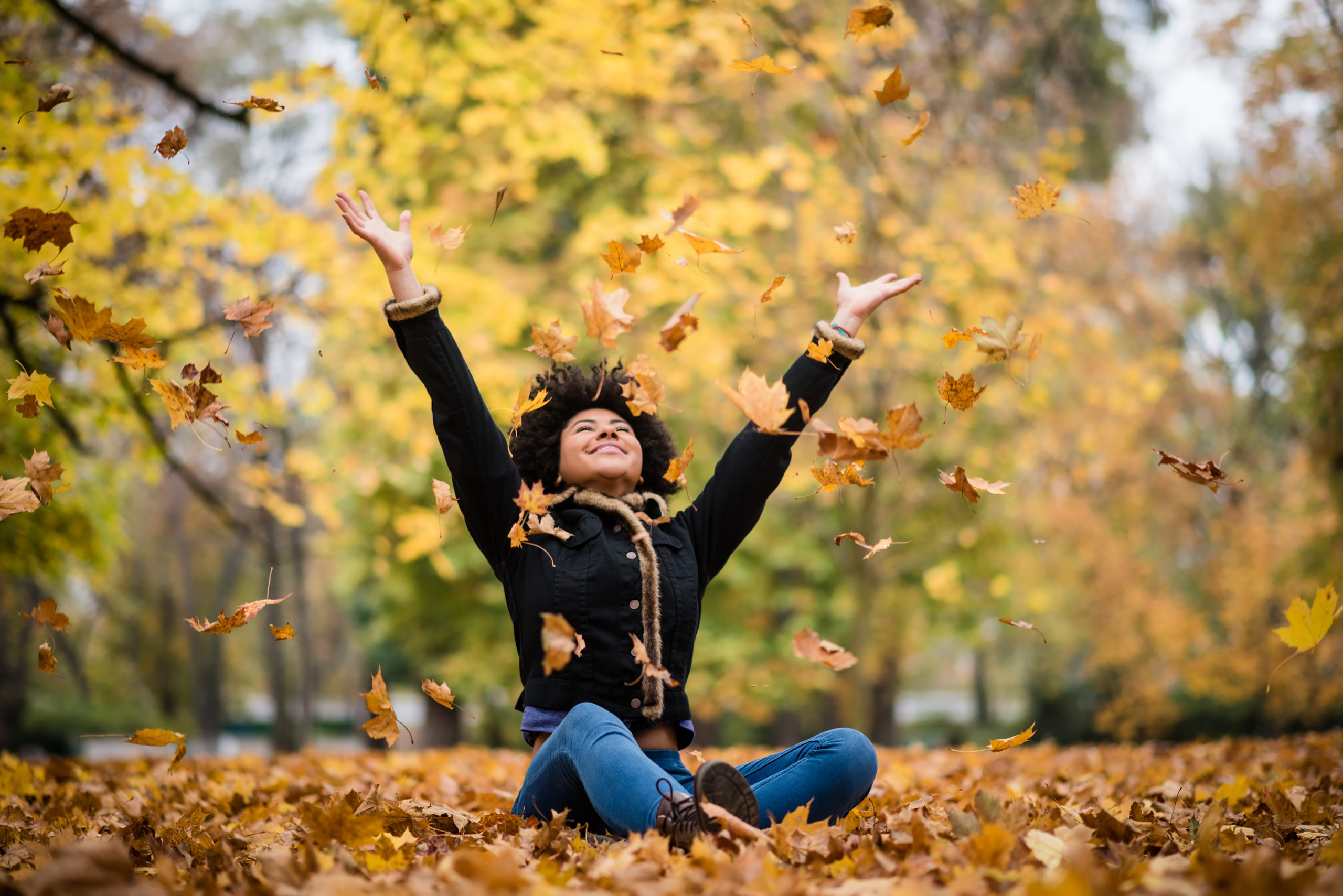 Happy woman in autumn park drop up leaves